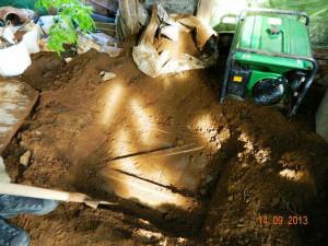 Вот под толстым слоем земли уже что-то появилось. Похоже на крышку погреба. Смотрим что там дальше.